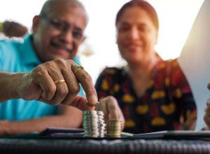 Senior Indian/asian couple arranging/staking coins/saving money