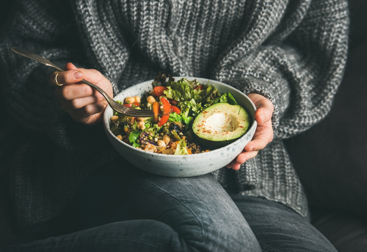 Healthy vegetarian dinner. Woman in grey jeans and sweater eating fresh salad, avocado half, grains, beans, roasted vegetables from Buddha bowl. Superfood, clean eating, dieting food concept (Healthy vegetarian dinner. Woman in grey jeans and sweater