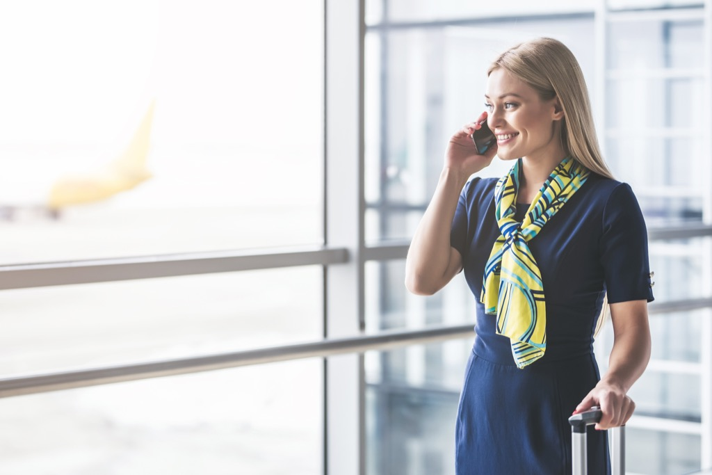 smiling flight attendant in terminal with suitcase