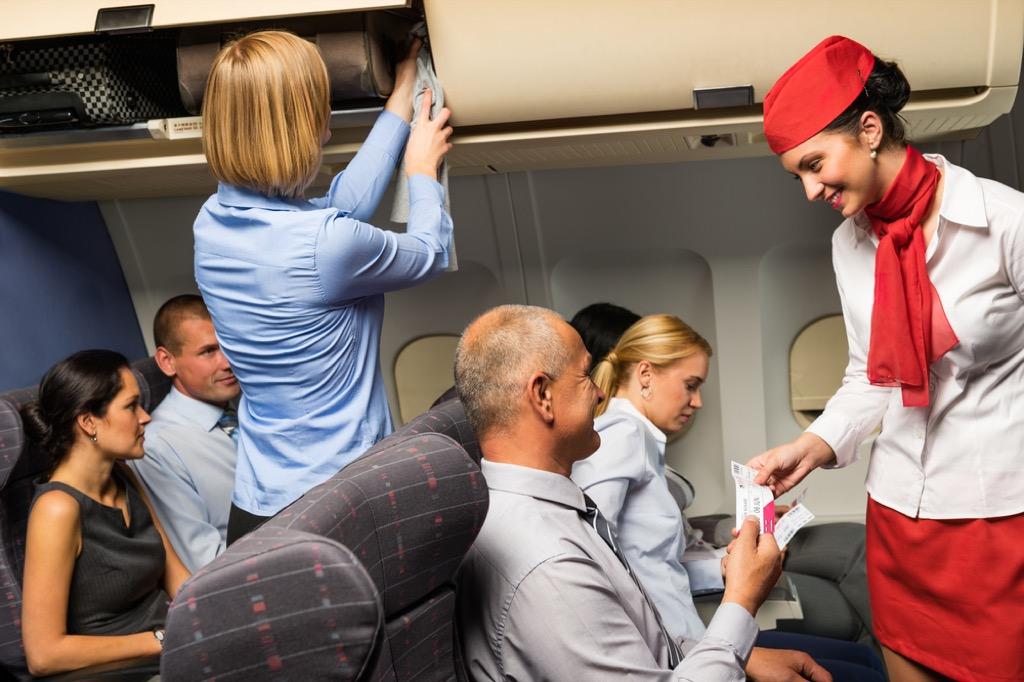 flight attendant talking to passenger