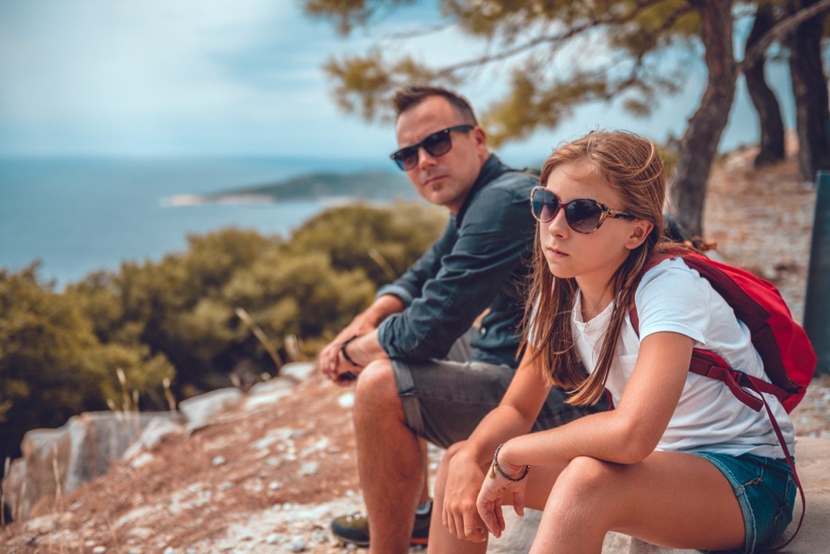 father and daughter sitting on rocks after hiking with each other