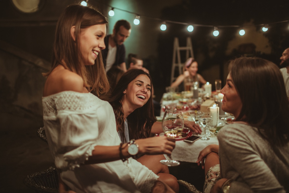smiling girlfriends at a dinner party with wine