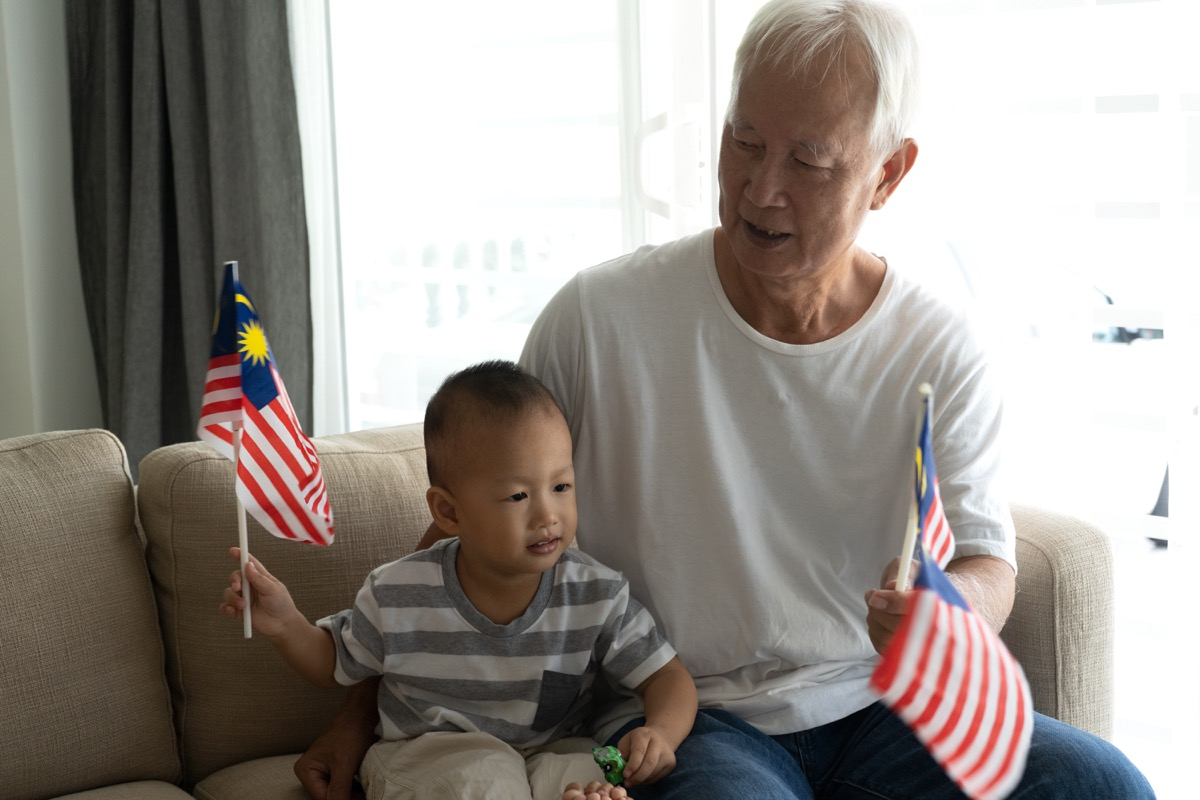 Grandfather with grandson holding Malaysian flags