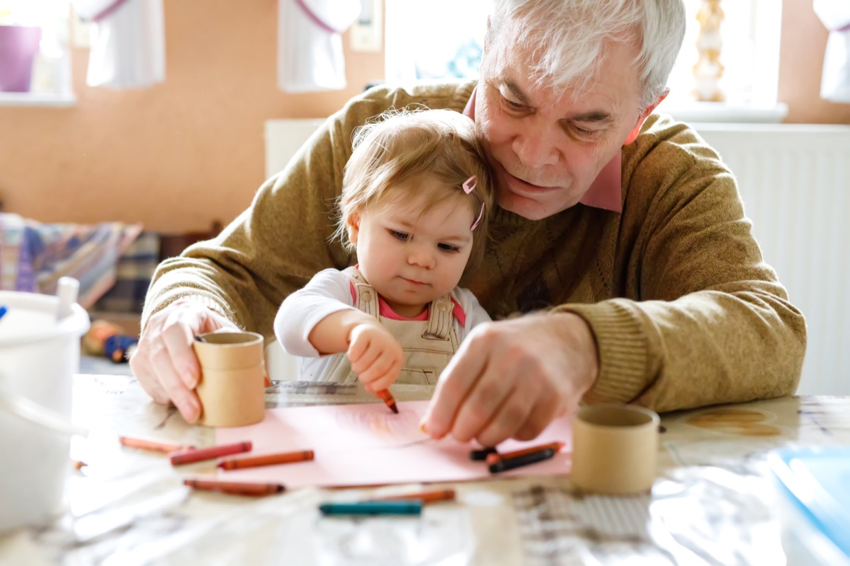 Grandfather drawing with baby granddaughter