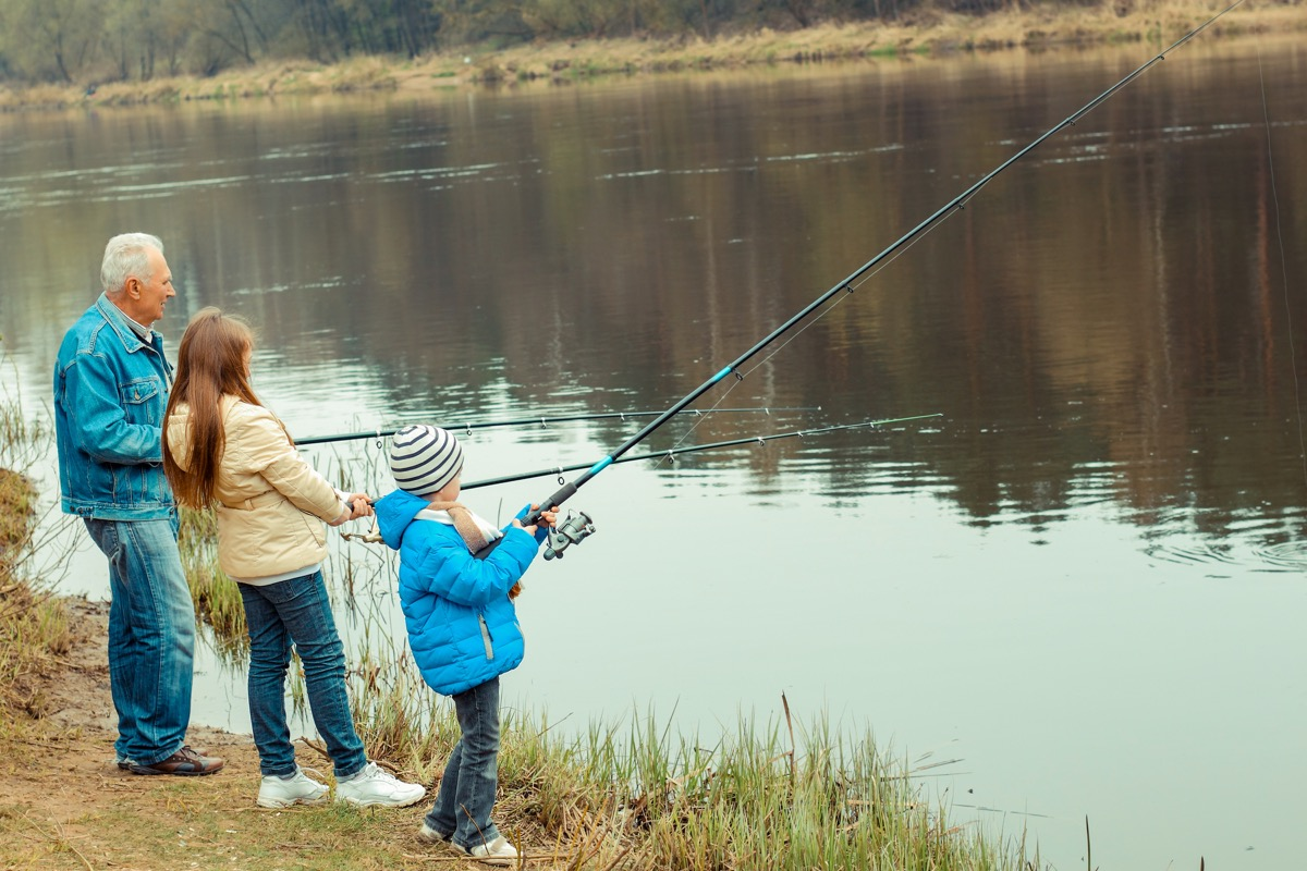 Grandfather fishing with his granddaughters