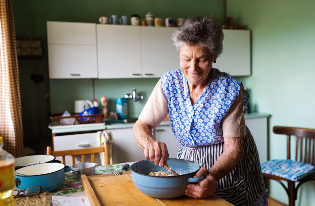 Old woman, grandma in the kitchen cooking