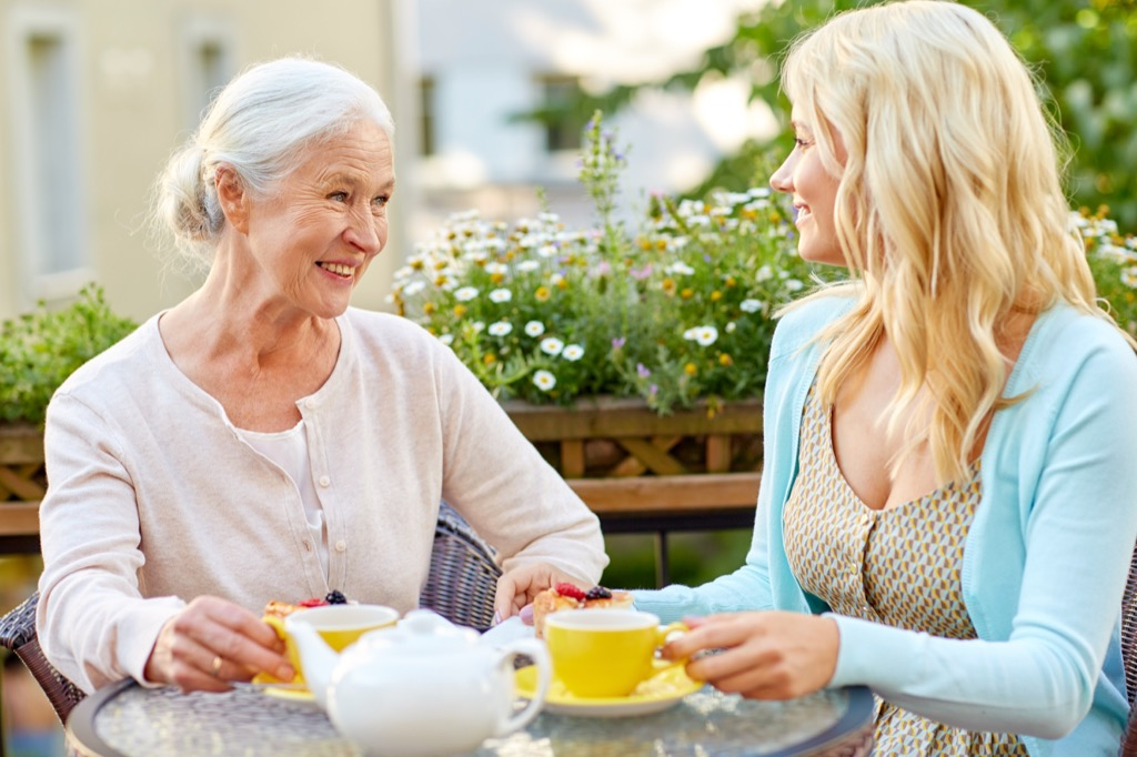 Grandma, older mom sitting down with her grown adult daughter for a drink