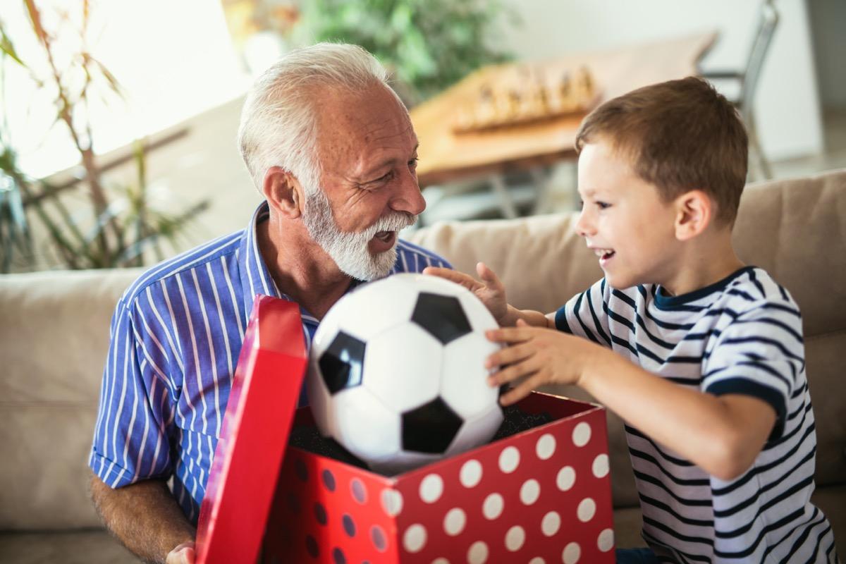 Grandpa giving grandson soccer ball