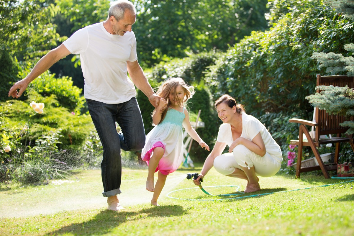 Grandpa running with granddaughter while grandmother waters the grass