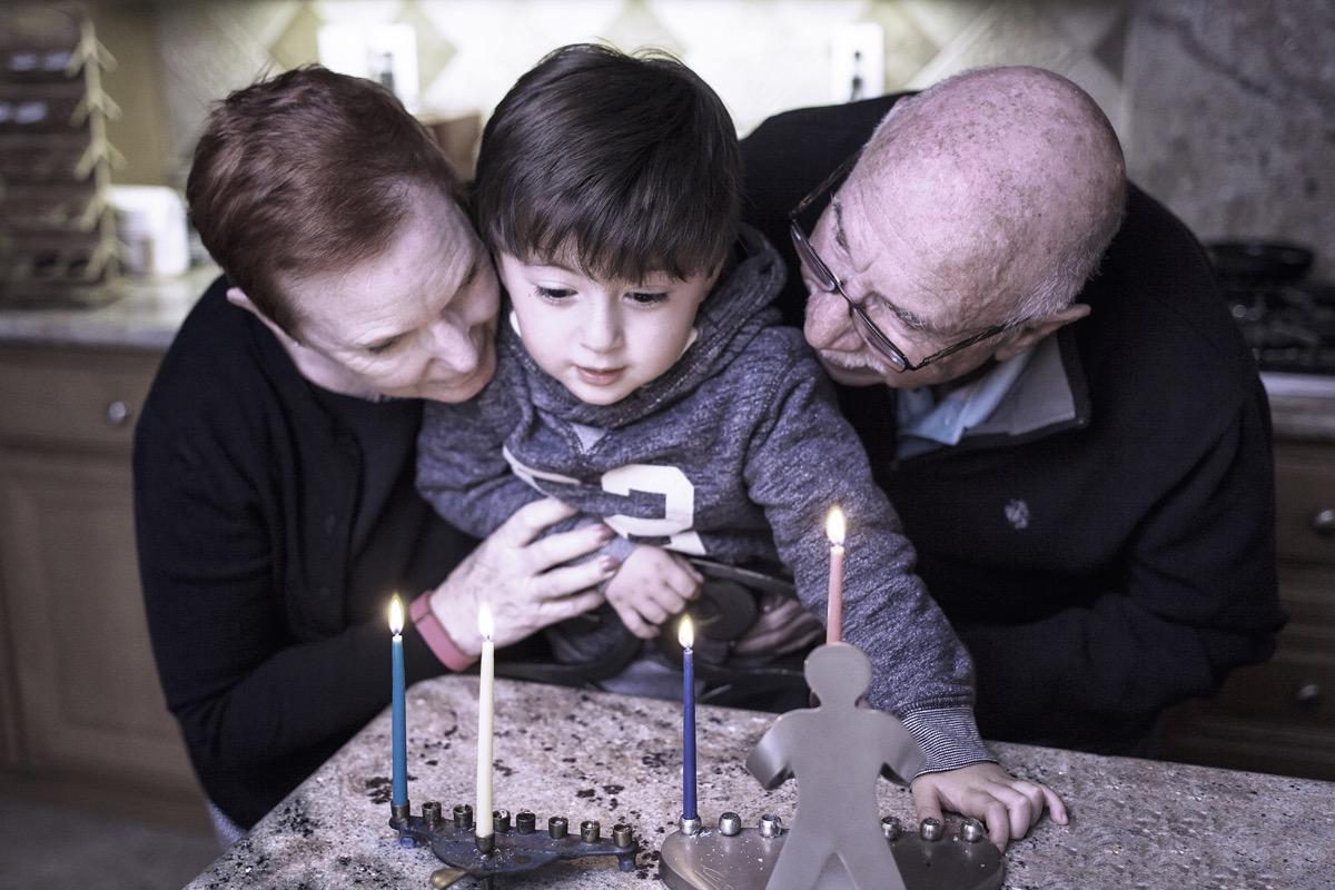 Jewish grandparents lighting the menorah with grandchild