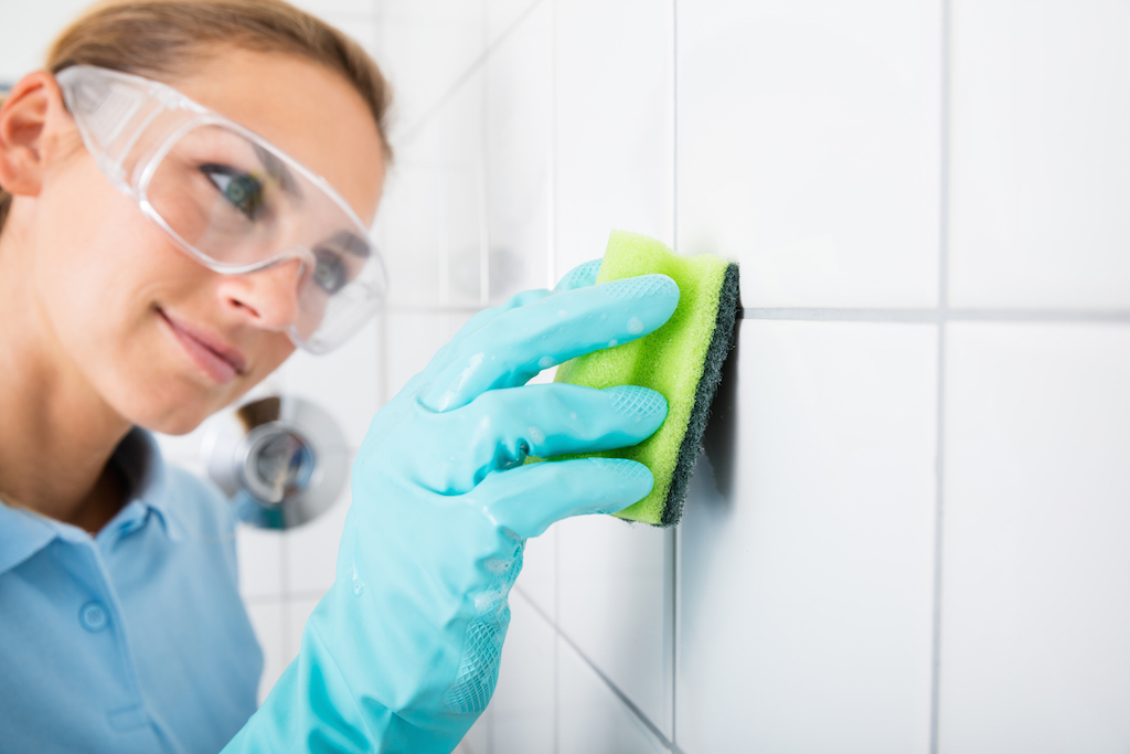 Woman cleaning the grout on the tile walls