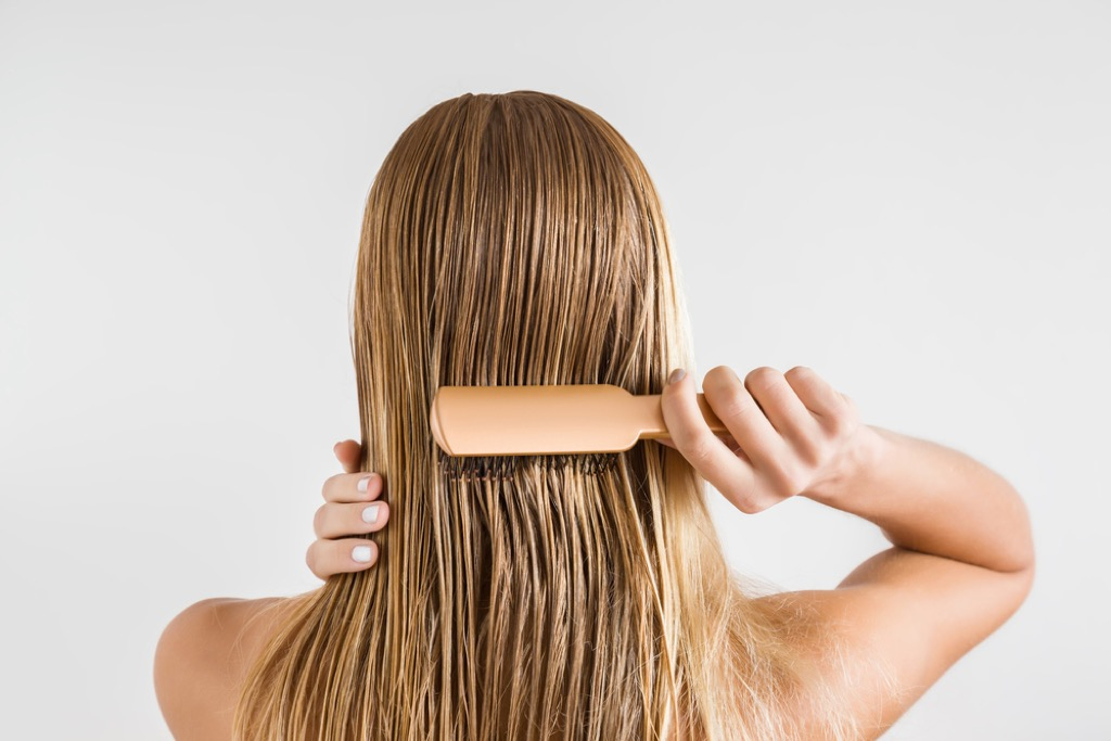 Woman Brushing Hair Signs Your Hair Will Go Gray