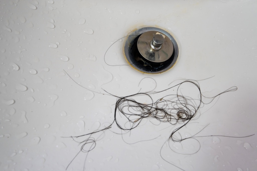 clogged drain and clump of hair, things housekeepers hate