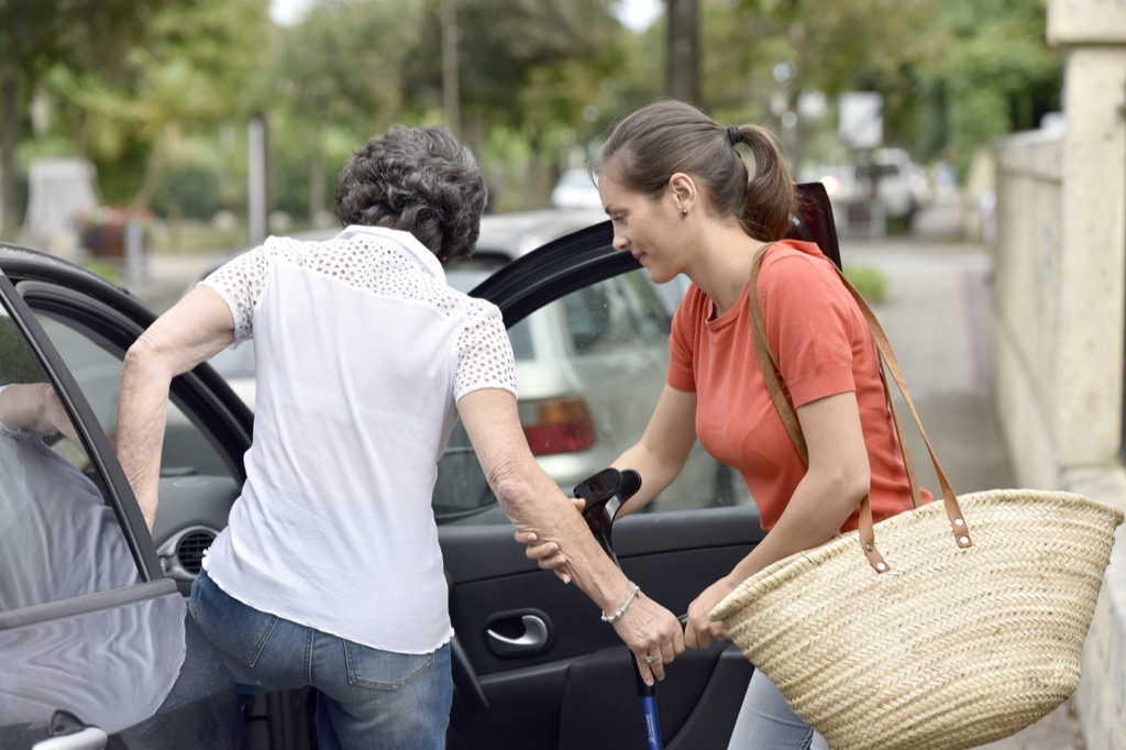 Woman helping a senior citizen get into the car