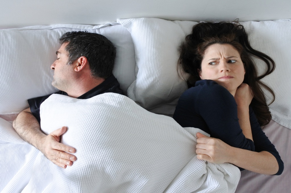 Man in couple is hogging all the blanket in bed