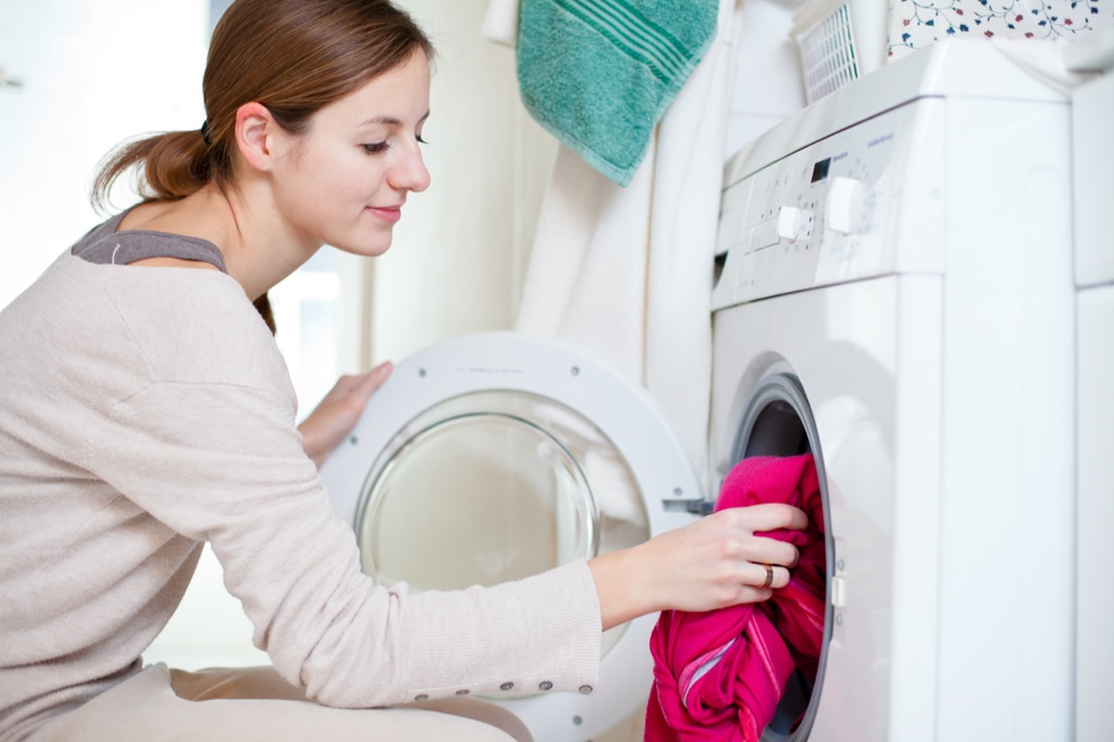 Woman loading the washing machine with laundry