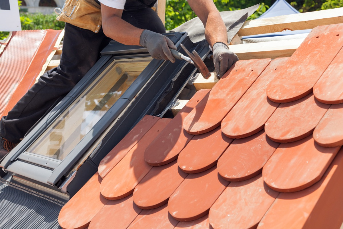 Man laying new tile on the roof