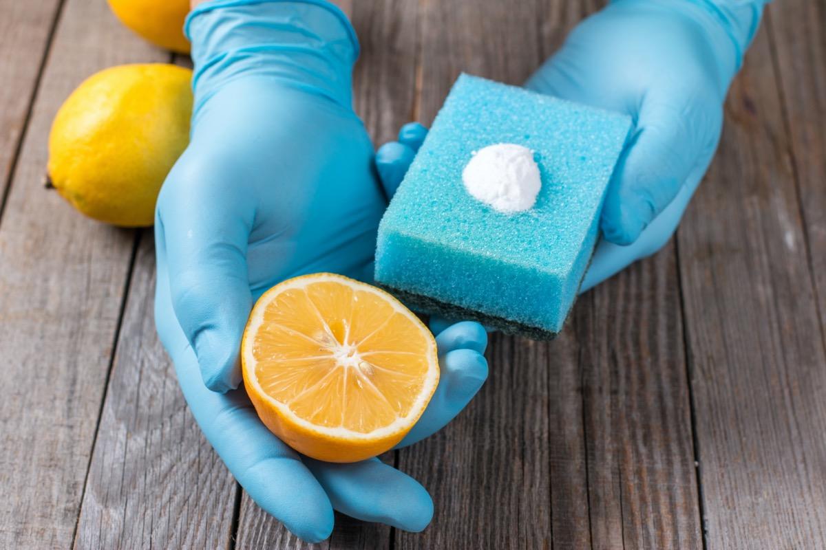 gloved hands holding sponge and lemon