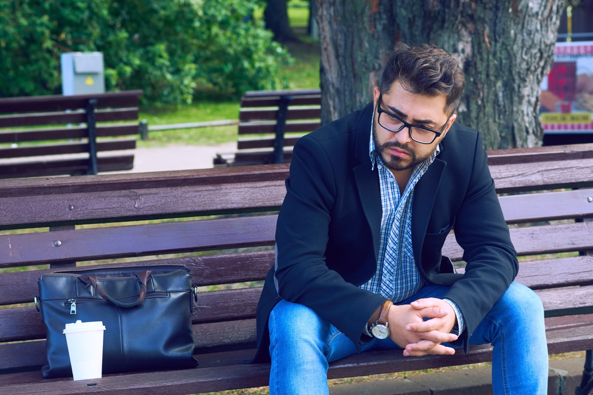 young man in glasses sitting on a bench in the park with sad facial expression. Office worker lost his job. Middle aged man despair economic crisis.