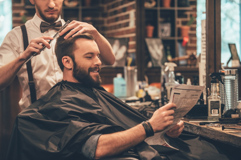 a man getting a haircut in a barber shop
