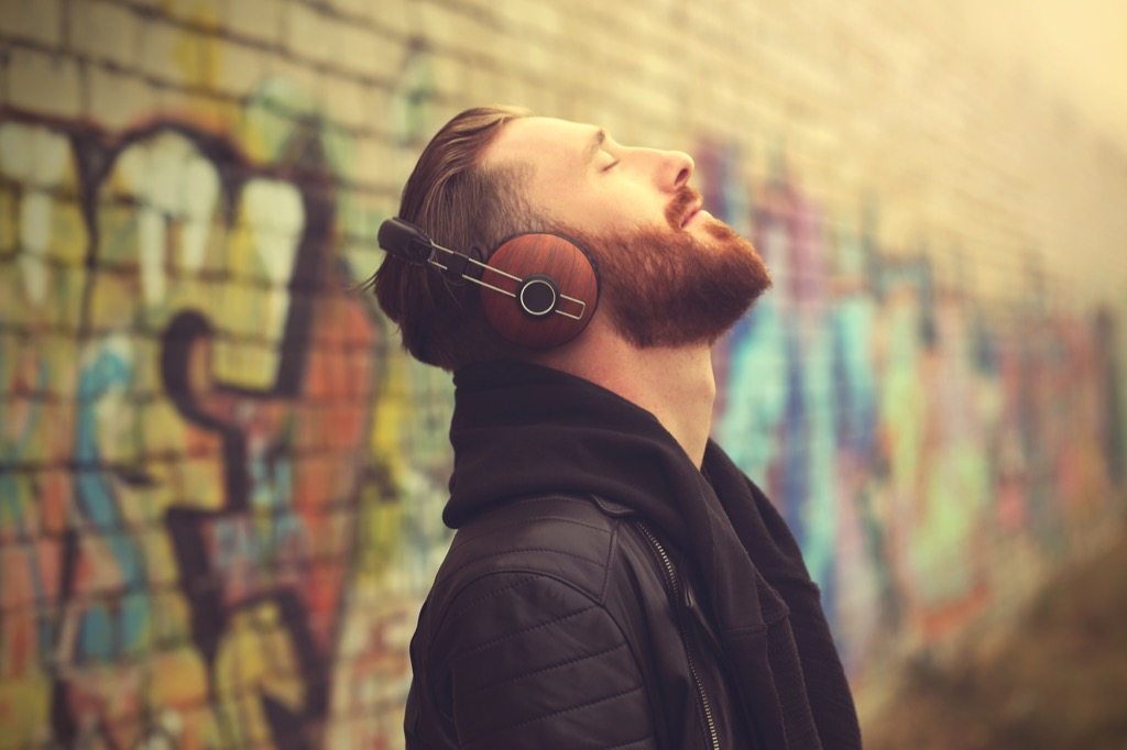 man listening to music on headphones outside in front of a brick wall