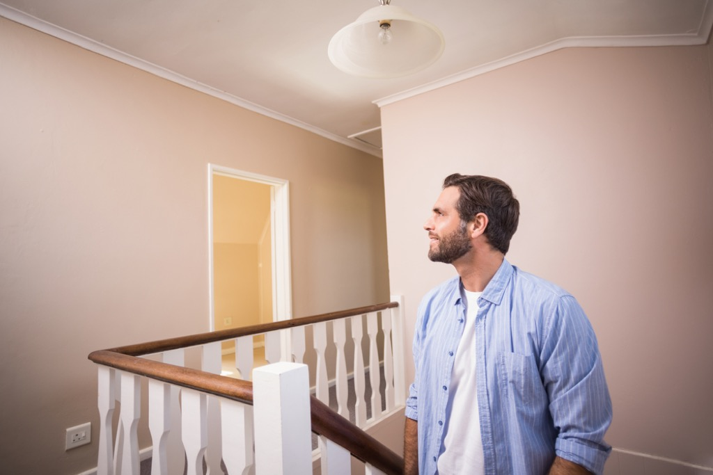 man walking up stairs in house