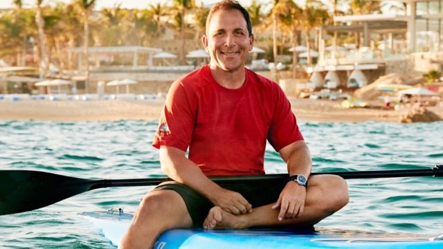 mike meldman sitting on a surfboard