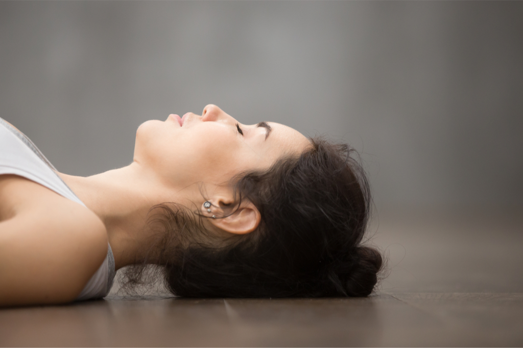Woman lying on floor with eyes closed
