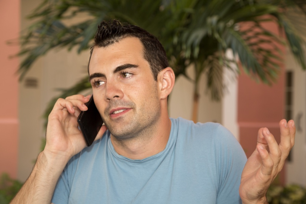 Man is on the phone shrugging, signs you're in love with someone else