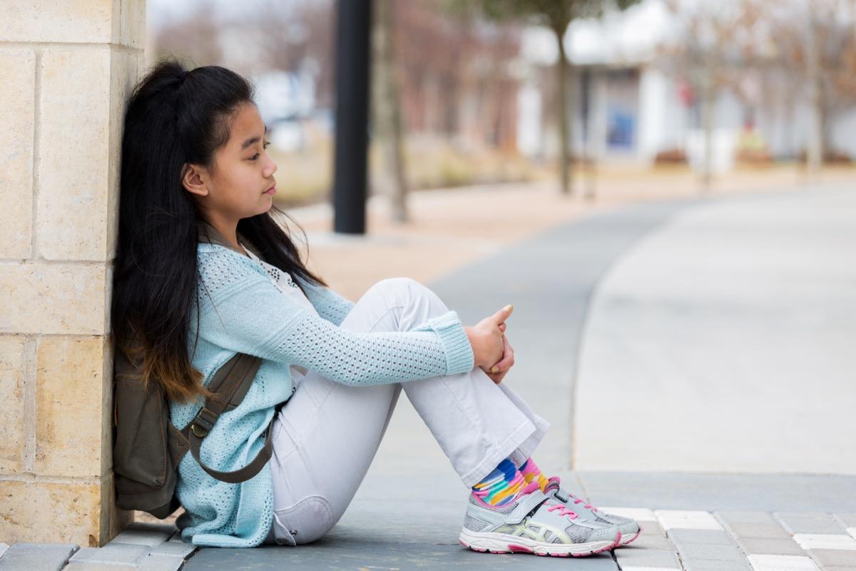 sad girl sitting outside on the sidewalk of her elementary school by herself