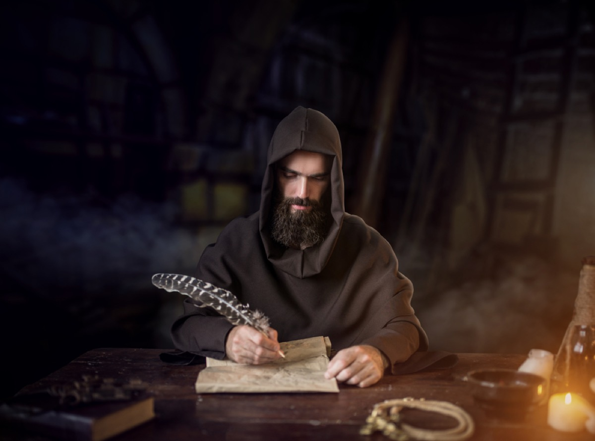 medieval monk writing on a scroll
