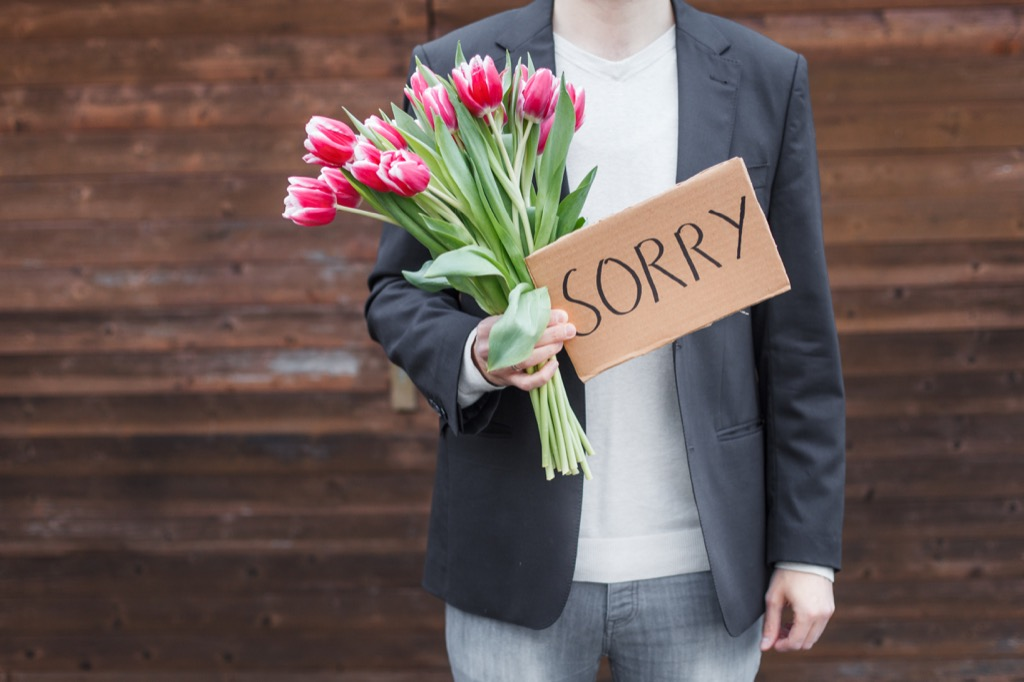 man holding flowers and sign that reads sorry