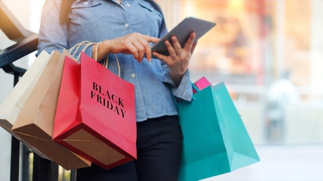 """woman shopping on black friday with bag that says """"black friday"""" on it"""