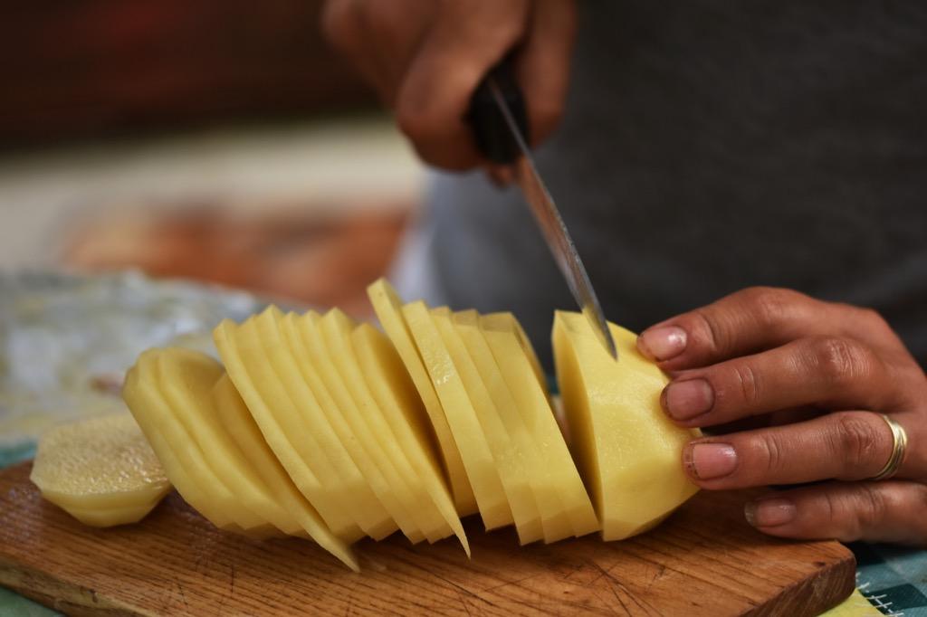 a man slicing a peeled potato