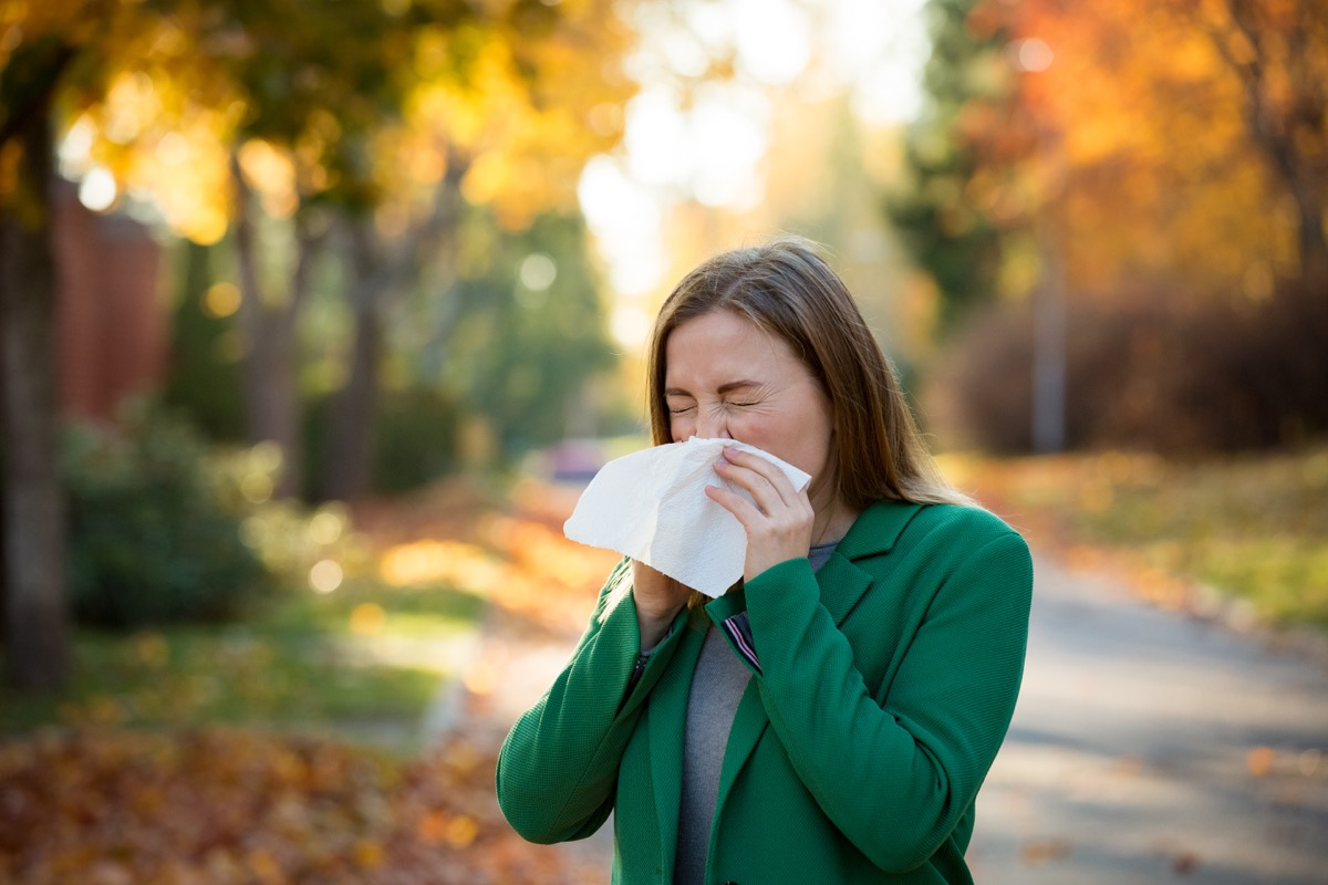Woman sneezing into a tissue or handkerchief