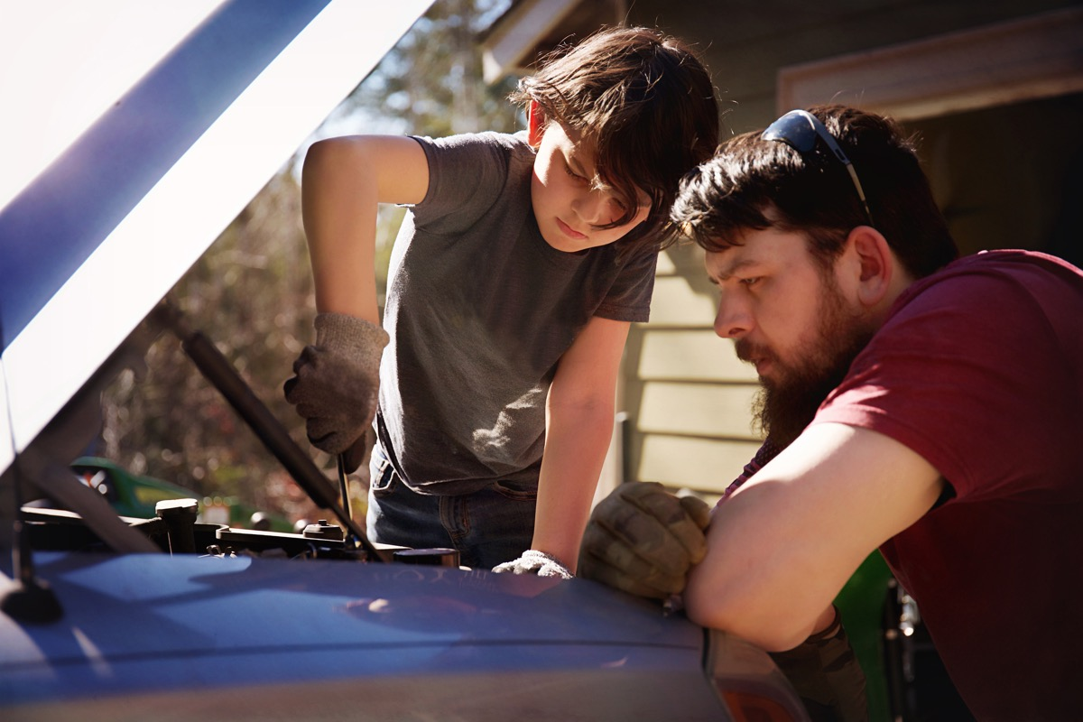 father teaching his son how to work on the motor of a car