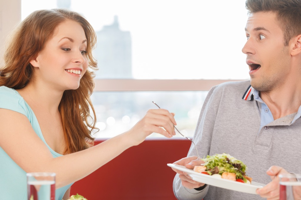 Woman stealing a bite of food from her boyfriend's plate