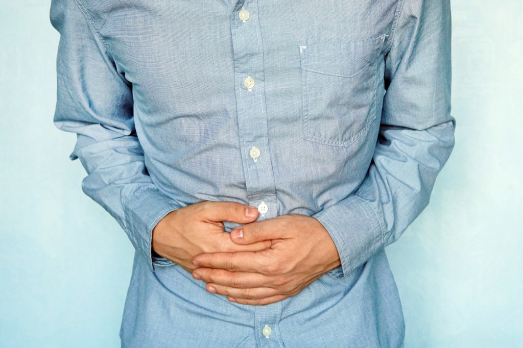 Rumbling stomach, man holding his stomach in pain