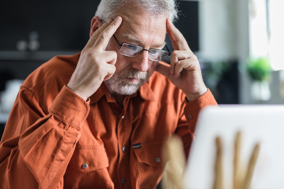 Mature businessman reading a problematic e-mail on laptop.
