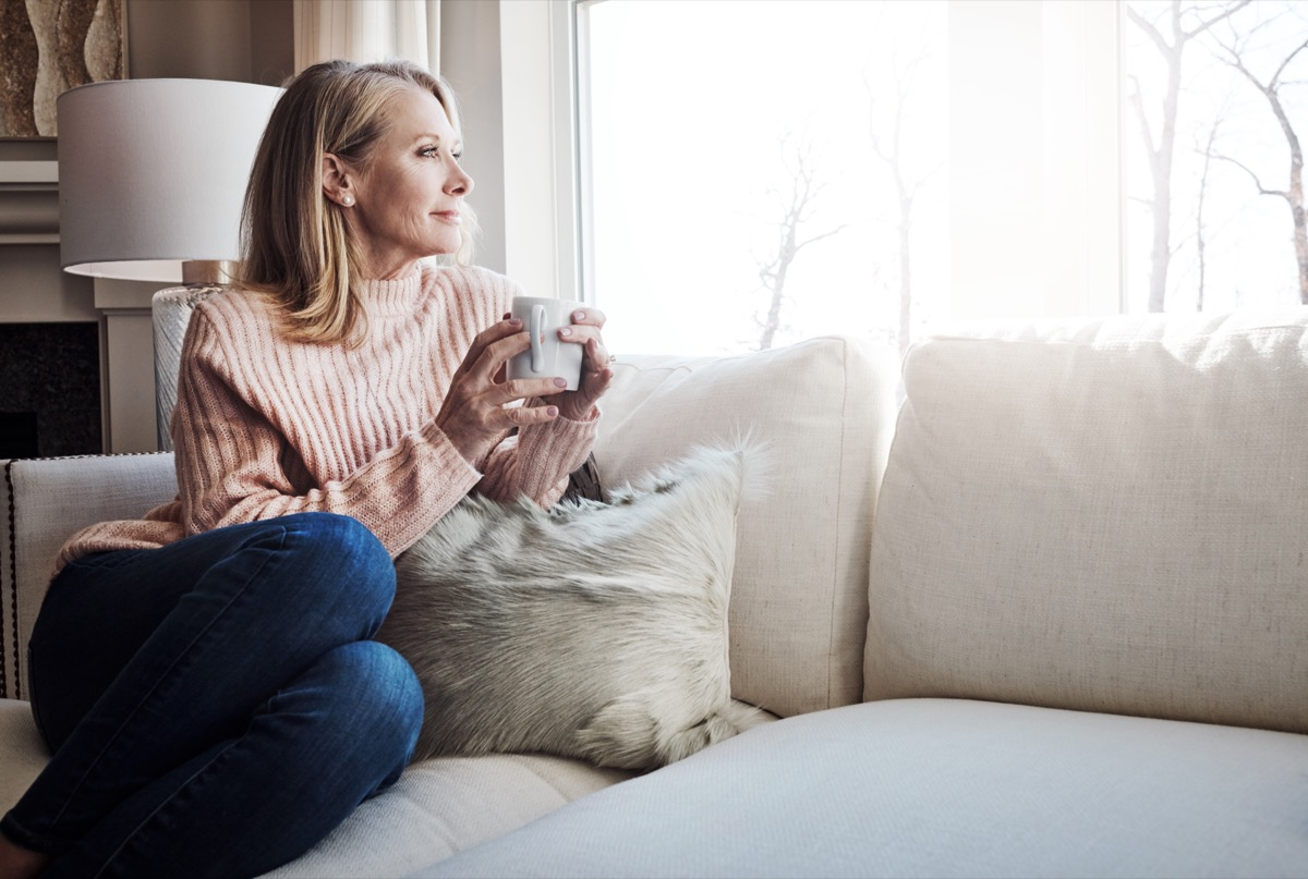 woman sitting alone on the couch sipping coffee