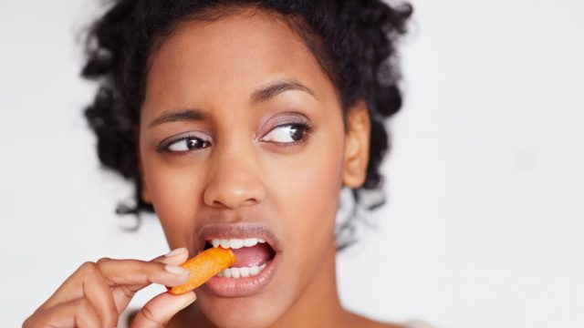 Diet - Closeup portrait of a sad African American female eating a carrot