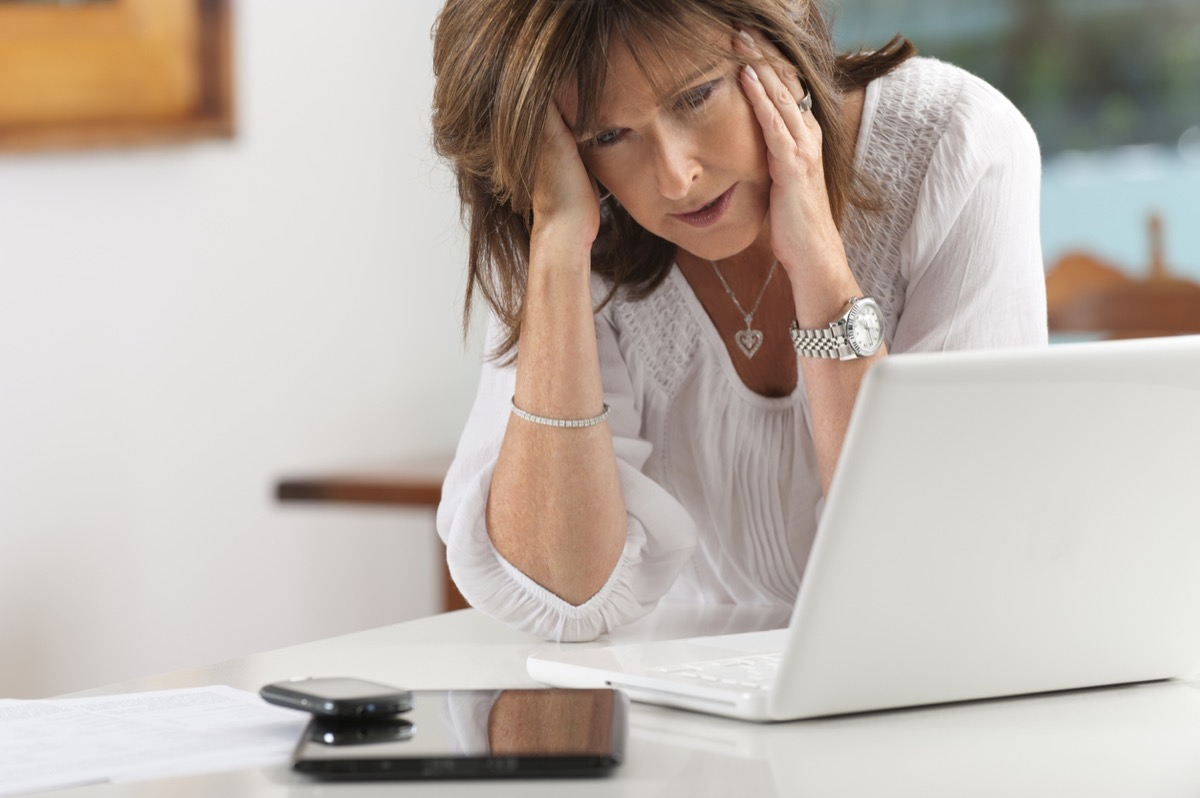 Worried middle-aged woman with technology at home