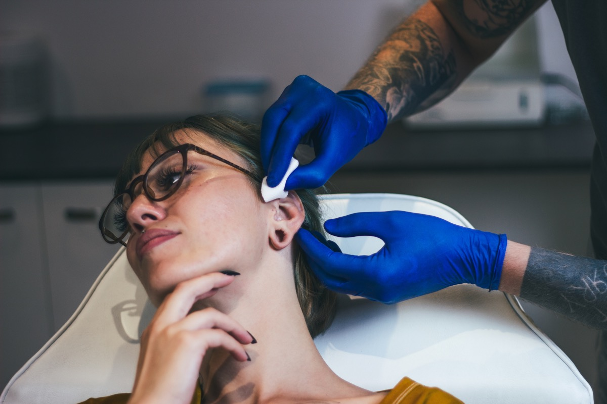 Young Woman getting her ear pierced. Man showing a process of piercing with steril medical equipment and latex gloves. Body Piercing Procedure (Young Woman getting her ear pierced. Man showing a process of piercing with steril medical equipment and la