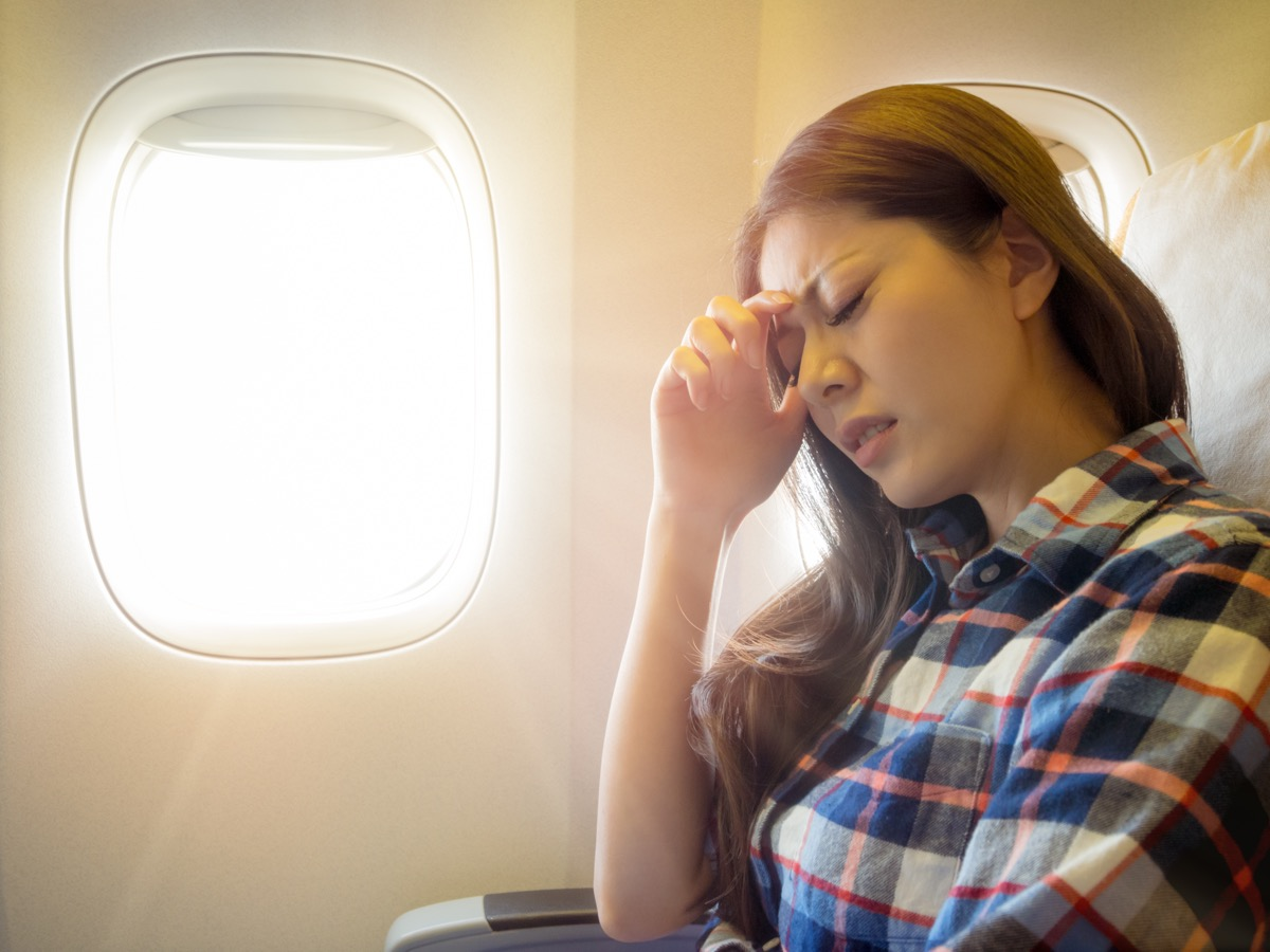 Woman holding her head with a headache on an airplane