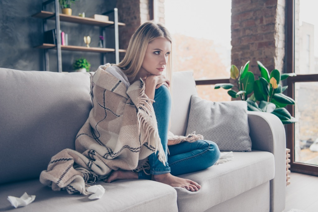 woman wrapped in blanket on a couch