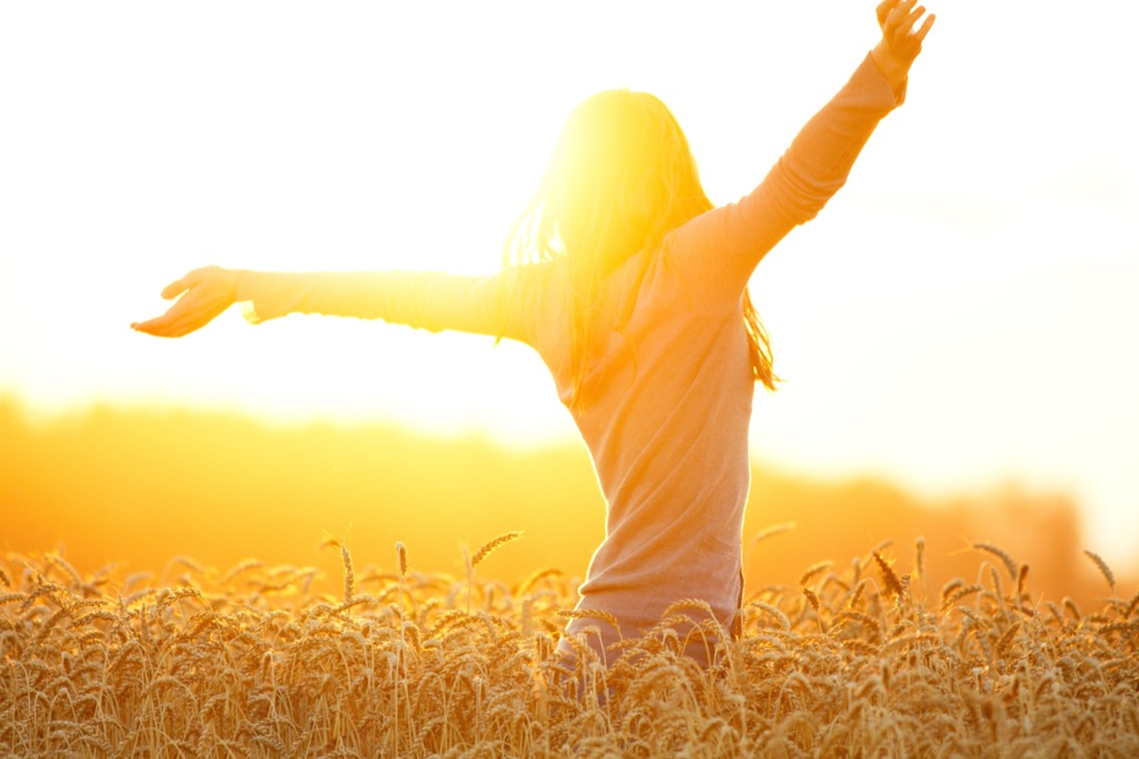 an optimistic woman in a field on a sunny day