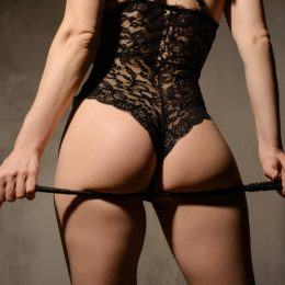 woman in lingerie holding a whip engaging in erotic spanking