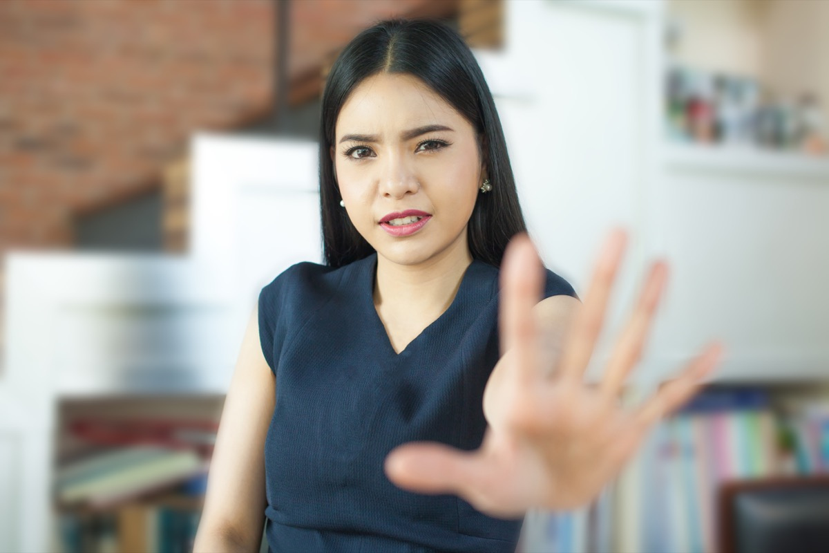 Asian woman putting her hand up and saying no