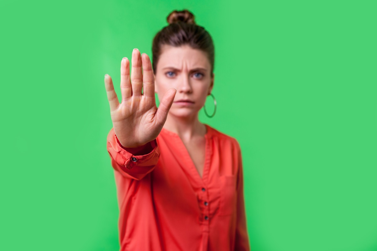 Stop, no! Portrait of angry or worried young woman with bun hairstyle, big earrings and in red blouse frowning gesturing caution to camera, prohibition. indoor studio shot isolated on green background (Stop, no! Portrait of angry or worried young woma