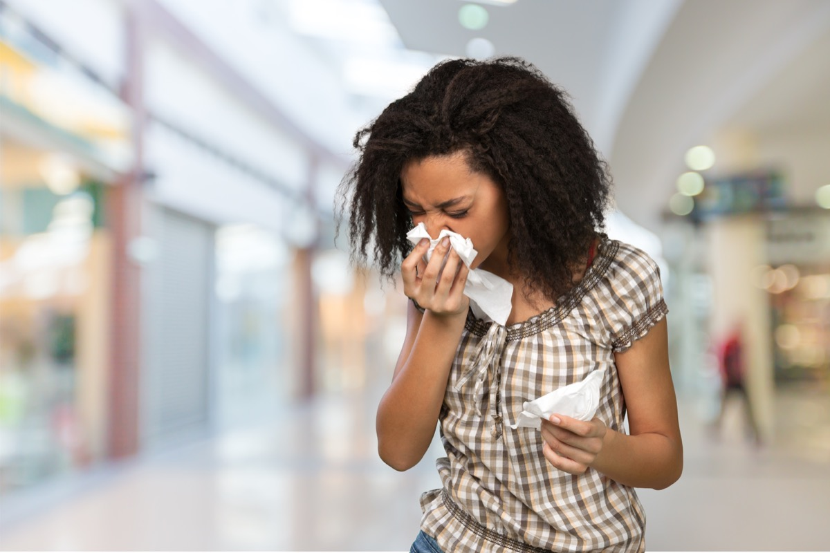 Woman blowing her nose after sneezing